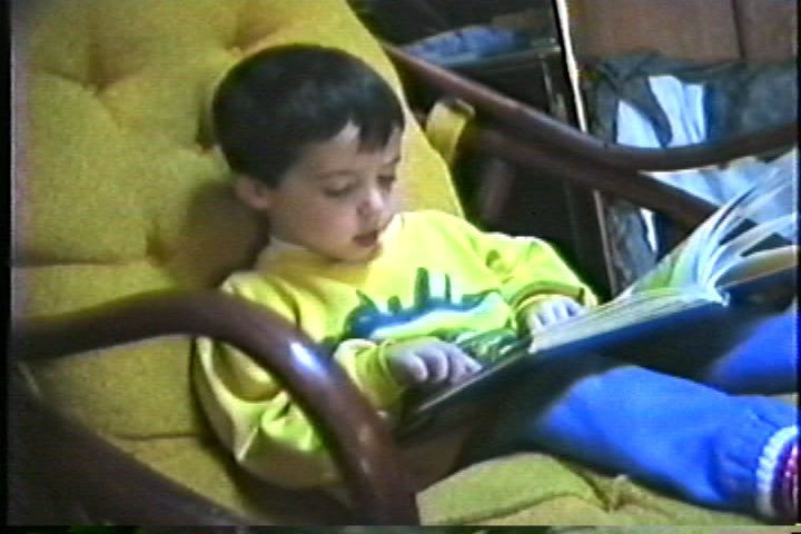 A kid reading a book in a yellow chair