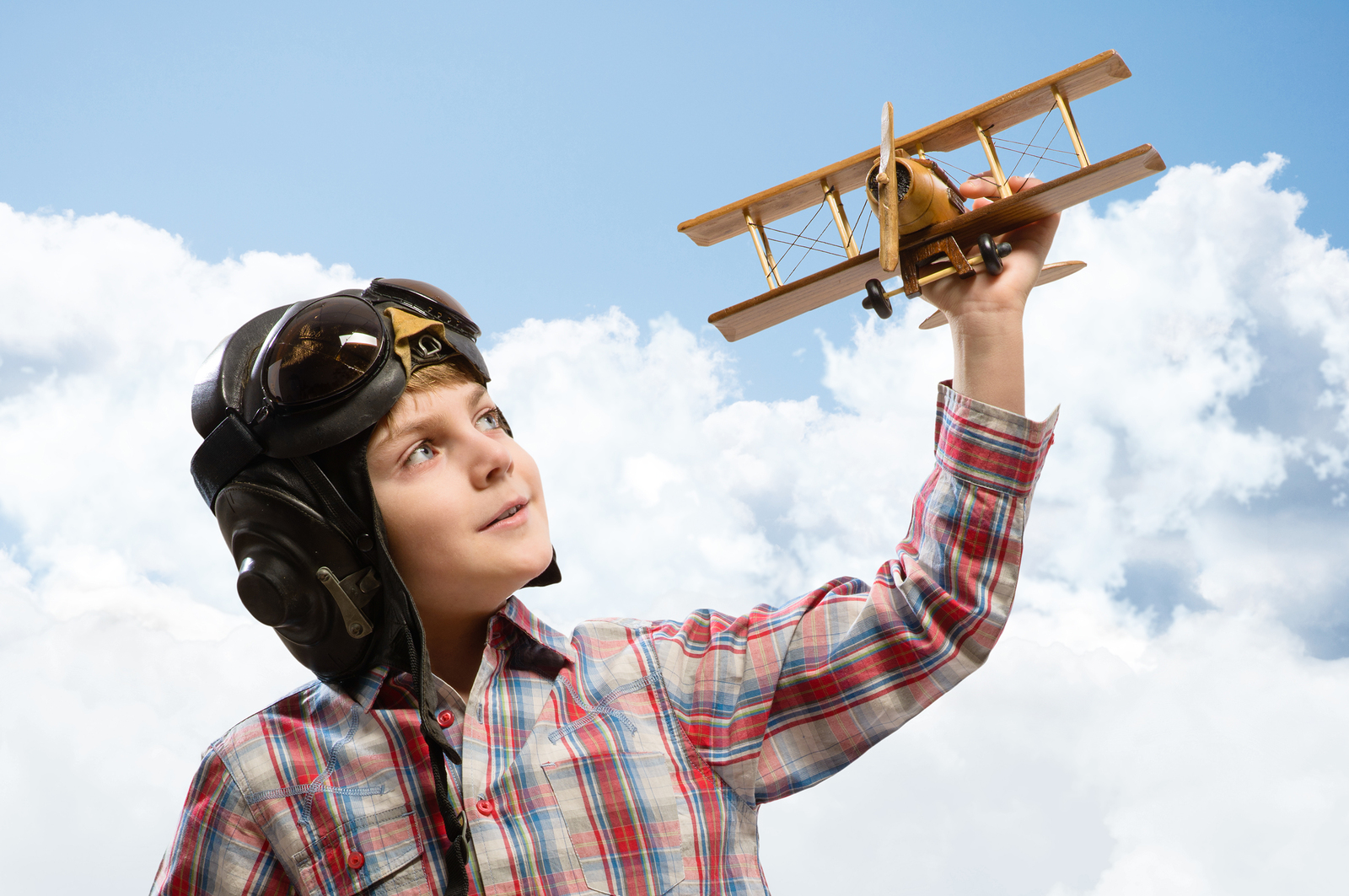 Young Boy With Pilot Helmet Playing a Plane Toy