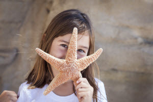 Beautiful Young Child Holding a Big Starfish