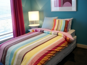 A Beautiful Kid's Bed with Rainbow Colored Bed Sheet