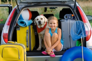 A Little Girl and Her Dog at the Back of the Car with Luggage
