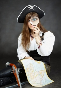 Woman pirate, and map with a magnifying glass.