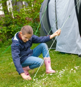 A young girl building Tent on the Camp SIte