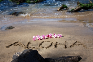 The Word Aloha Written on Sand by the Sea Shore