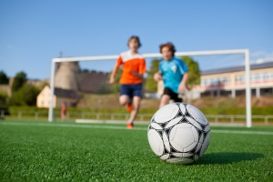 two young soccer players running to the soccer ball