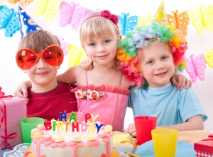 Three Children with a Birthday Cake on a Clown Themed Birthday Party