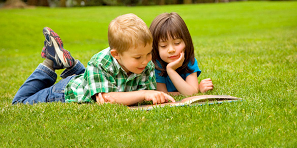 two kids studying on the lawn