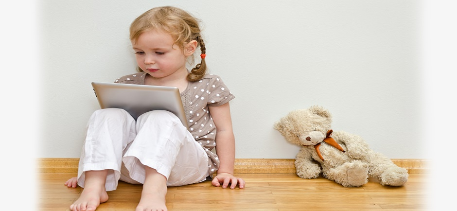 Cute little girl reading on an ipad with bear